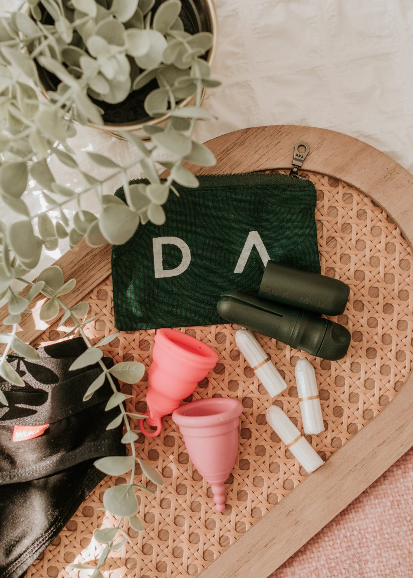 Flatlay image showing a re-useable tampon applicator, organic tampons, menstrual cups and period pants laid on a ratten tray.